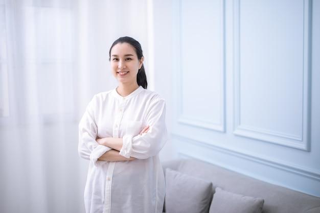 아름다운 미소와 팔로 카메라를 바라보는 긴 검은 머리를 가진 멋진 아시아 여성의 초상화