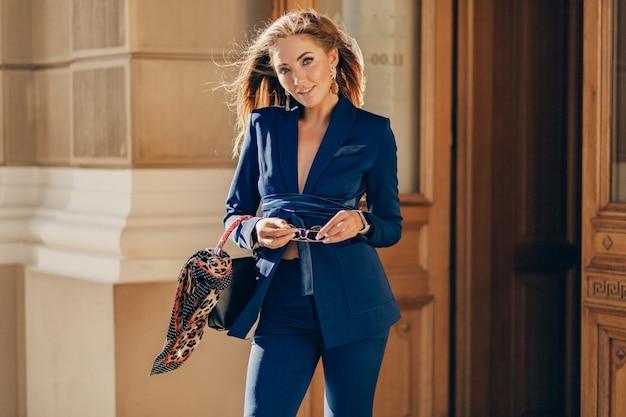 도시에서 걷는 우아한 파란색 정장을 입고 화려한 매력적인 웃는 여자의 초상화