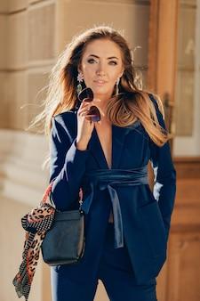 街を歩くエレガントな青いスーツに身を包んだゴージャスな魅力的な笑顔の女性の肖像画