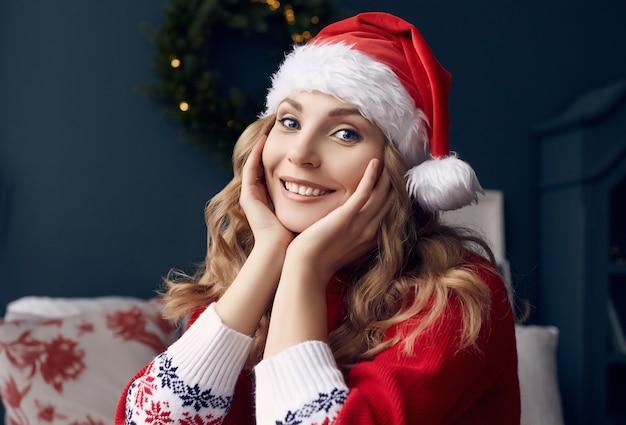 Портрет великолепной блондинки в красном свитере и шляпе санты весело в постели и позирует в рождественском интерьере.