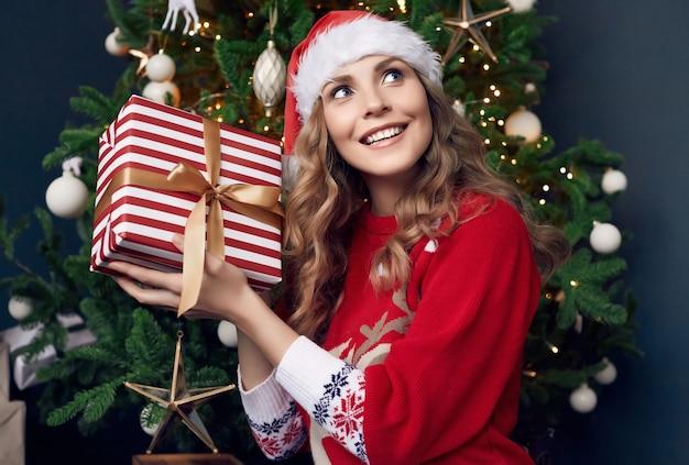 Портрет великолепной блондинки в красном свитере и шляпе санты, держащей подарок в рождественском интерьере.