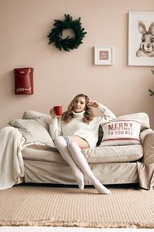 밝은 아늑한 장식 된 인테리어에 뜨거운 커피를 마시는 흰색 모직 스웨터에 화려한 금발 여자의 초상화