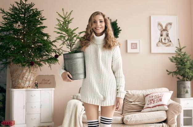 밝은 아늑한 장식 인테리어에 화분에 심은 전나무 나무와 함께 포즈 흰색 모직 스웨터에 화려한 금발 여자의 초상화