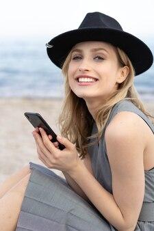 携帯電話を持って、ビーチで帽子をかぶって完璧な笑顔でカメラを見てゴージャスな金髪の若い女性の肖像画