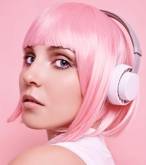 분홍색 머리를 가진 화려한 밝은 힙 스터 소녀의 초상화는 다채로운 헤드폰에서 음악을 즐깁니다.