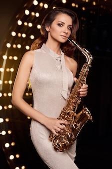レストランのステージのスポットライトでサックスを演奏するエレガントなドレスを着たゴージャスなブルネットモデルの女性の肖像画。