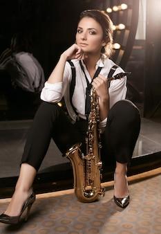 サックスを演奏するファッショナブルなフォーマルなスーツを着たゴージャスなブルネットモデルの女性の肖像画