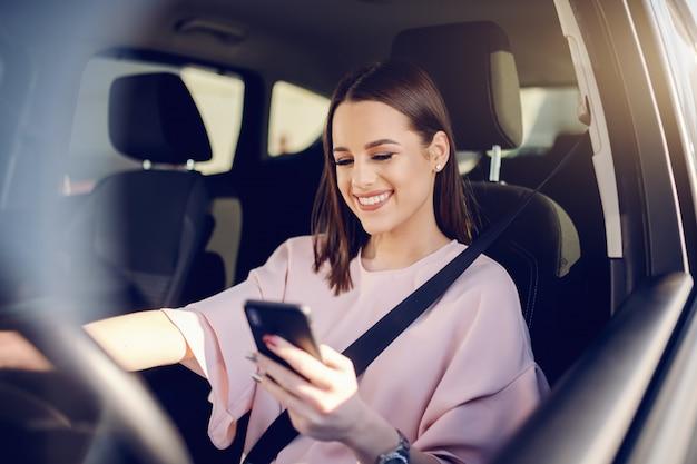 車を運転してスマートフォンを使用して歯を見せる笑顔でゴージャスなブルネットの肖像画。