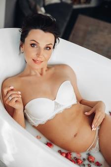 カメラに微笑んで、白いランジェリーのバラとお風呂でポーズをとって赤ちゃんを期待しているゴージャスなブルネットの女性の肖像画。