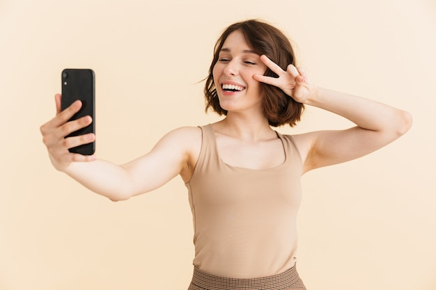 Портрет великолепной кавказской женщины 20-х годов, одетой в повседневную одежду, показывает знак мира во время селфи-фото на изолированном мобильном телефоне