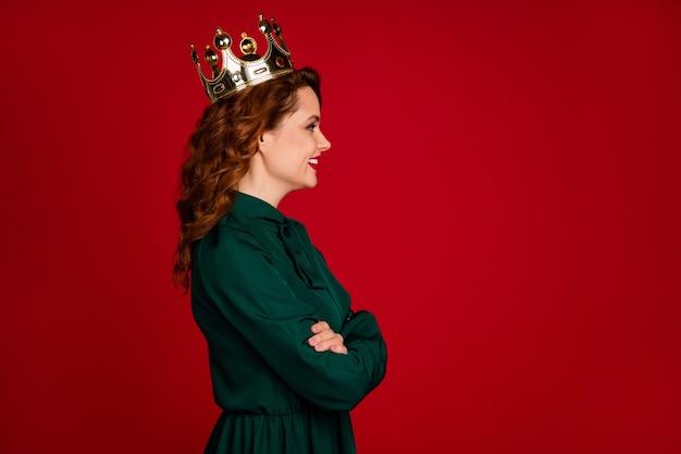 赤いマルサラ色の背景に分離されたdiadem腕を組んでゴージャスな女の子の肖像画