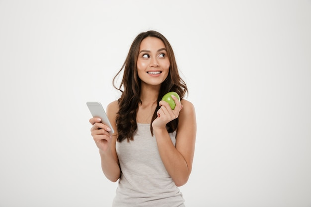 Портрет великолепной здоровой женщины, глядя в сторону, позирует на камеру с зеленым яблоком и смартфон в руках, изолированных на белой стене