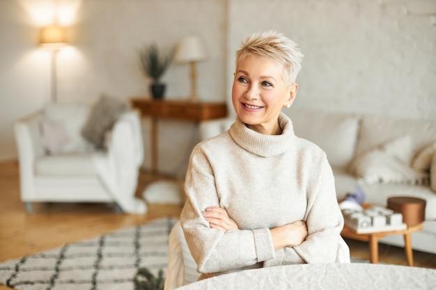 Портрет великолепной зрелой европейской женщины с короткой прической, расслабляющейся дома, сидя за столом в гостиной, скрещивая руки на груди, пытаясь согреться в уютном кашемировом свитере с высоким воротом, улыбаясь