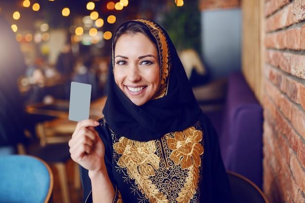 小切手を要求し、カフェに座っている間クレジットカードを保持している伝統的な摩耗に身を包んだ豪華なイスラム教徒の女性の肖像画。