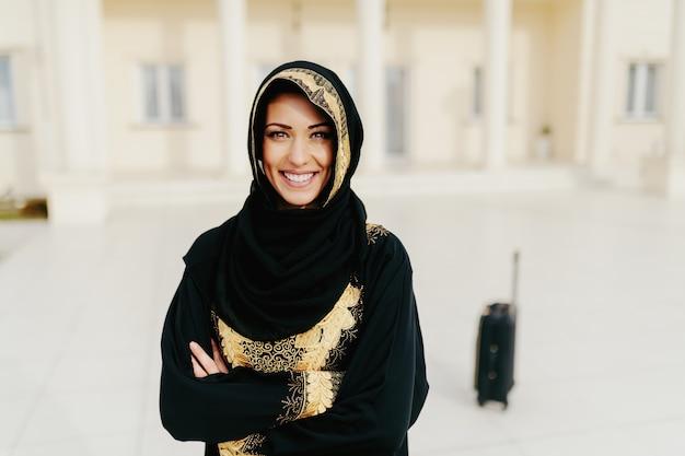 Портрет шикарной мусульманской женщины с зубастой улыбкой и оружия пересек положение. в фоновом режиме багаж.