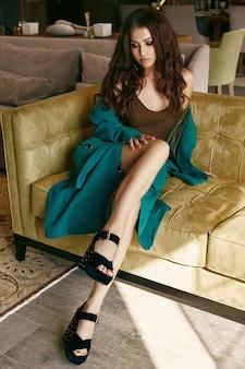 Портрет великолепной чувственной модели брюнетки в модном костюме, расслабляющемся на диване в гостиной.