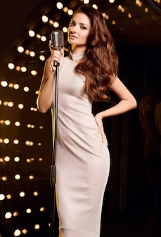 レストランのステージスポットライトにレトロなマイクとエレガントなドレスを着たゴージャスな歌手の女性の肖像画。