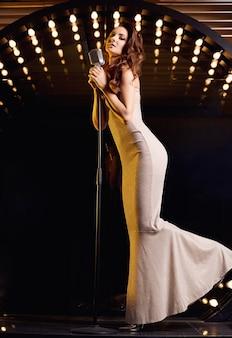 레스토랑 무대 조명에 복고풍 마이크와 우아한 드레스에 화려한 가수 여자의 초상화.