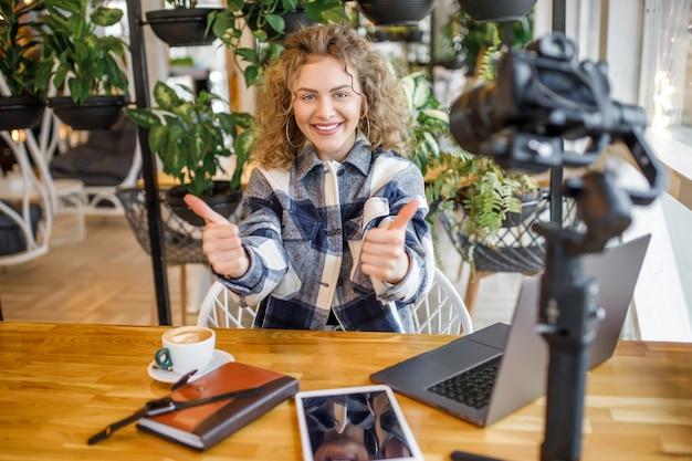 カメラにポーズをとって笑顔のカジュアルな服装でゴージャスな女性ブロガーの肖像画