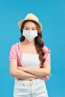 スタジオに立っている間フェイスマスクと帽子を身に着けているゴージャスな女性の肖像画