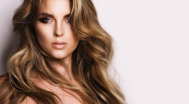 Портрет великолепной женщины с красивыми вьющимися волосами и профессиональным макияжем