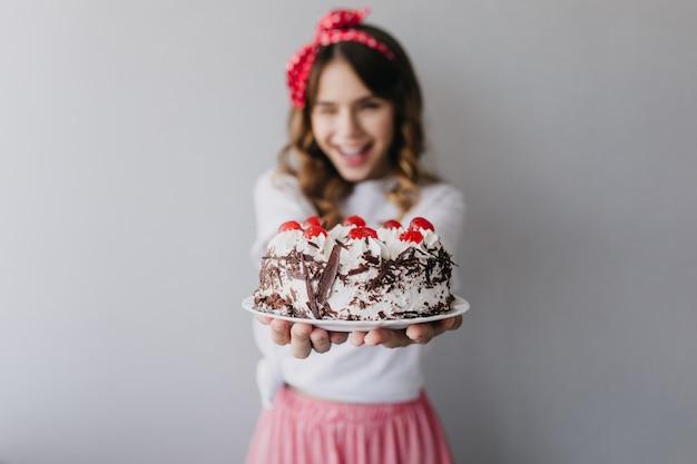 手前にクリーミーなケーキとゴージャスな女性の肖像画。孤立した気さくな誕生日の女の子。