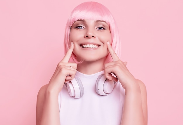 ピンクの髪のゴージャスな女性の肖像画は、ヘッドフォンで音楽を楽しんでいます