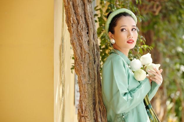 白い蓮の流れを保持し、目をそらしているアオザイのドレスを着たゴージャスな若いベトナム人女性の肖像画