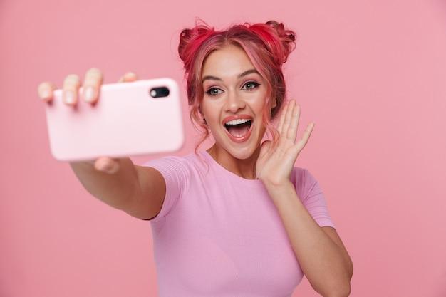 笑顔で携帯電話でselfie写真を撮る色の髪とtシャツのゴージャスな若い女性の肖像画