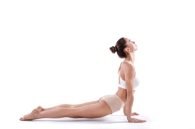 Портрет великолепной молодой женщины упражнениями йоги. красивая девушка практикует асаны кобры, изолированные на белом. спокойствие и расслабление.