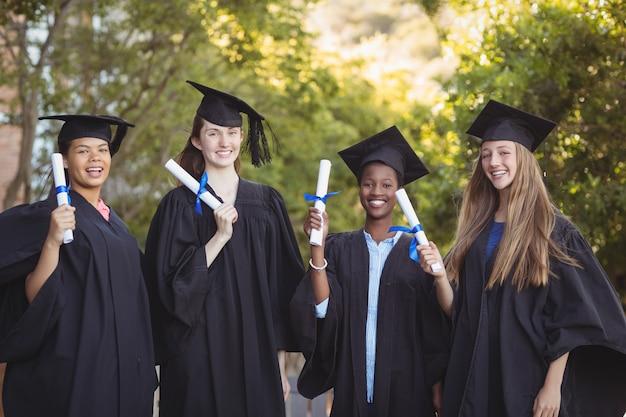 Портрет аспирантов, стоящих со свитком степени в кампусе