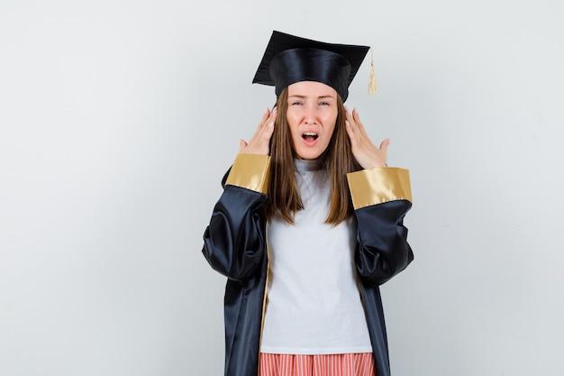 대학원 여자의 초상화 캐주얼 옷, 제복을 입고 머리 근처에 제기 손을 잡고 의아해 전면보기를 찾고