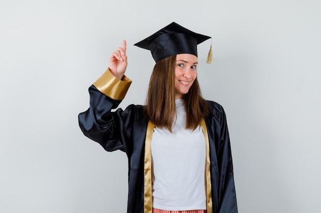カジュアルな服装で上向き、制服と陽気な正面図を探している大学院の女性の肖像画