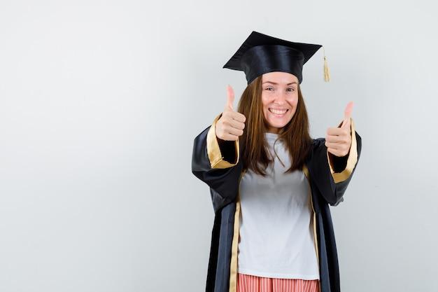 Портрет выпускницы, показывающей двойные пальцы вверх в повседневной одежде, униформе и блаженного вида спереди