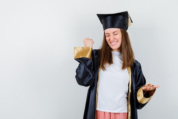 캐주얼 옷, 유니폼 및 유쾌한 전면보기에서 승자 제스처를 보여주는 대학원 여자의 초상화