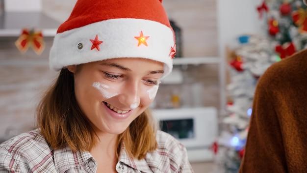 おいしいデザートを調理するサンタの帽子をかぶって顔に小麦粉を持つ孫娘の肖像画