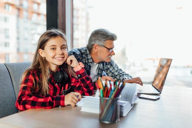 ノートパソコンと本で宿題をしている祖父と孫娘の肖像画