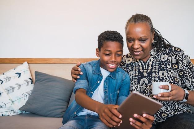 自宅のソファのソファに座ってデジタルタブレットで自分撮りをしている祖母と孫の肖像画。家族とライフスタイルの概念。
