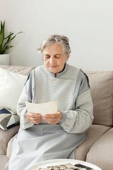 Портрет бабушки смотрит на старые фотографии