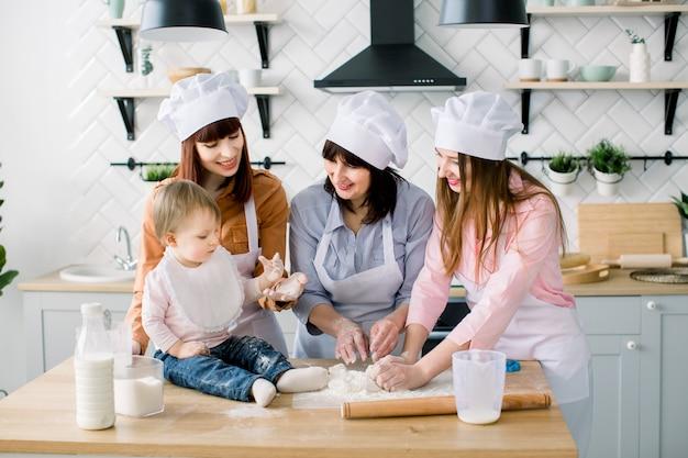 彼女の娘と孫娘が一緒にキッチンで夕食を作る祖母の肖像画。母の日のコンセプトです。