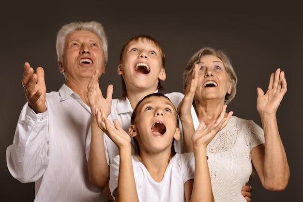 Портрет внуков с бабушкой и дедушкой на сером фоне