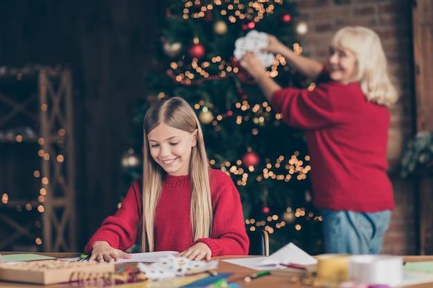 テーブルで飾られた家にお祝いの装飾を作成する紙のフレークをぶら下げおばあちゃんの孫の肖像画