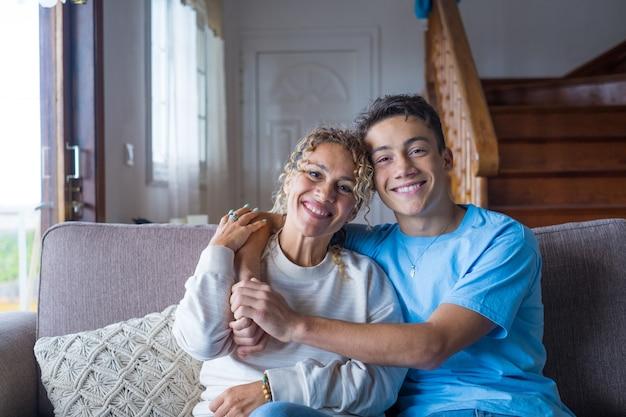 감사하는 10대 남자의 초상화는 웃고 있는 중년 어머니가 사랑과 보살핌을 보여주고, 행복한 성인 아들이 쾌활한 엄마를 껴안고, 주말 가족 시간을 집에서 함께 즐기고, 유대감을 형성하는 개념을 보여줍니다.