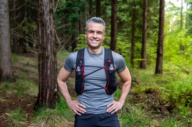 Портрет седого мужчины-трейлраннера, улыбающегося в камеру в лесу