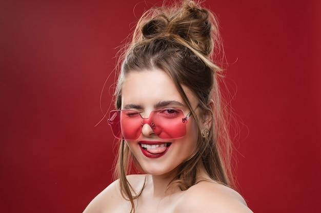 赤いサングラス、赤い背景で隔離の画像を持つ偉大なブロンドの女性の肖像画