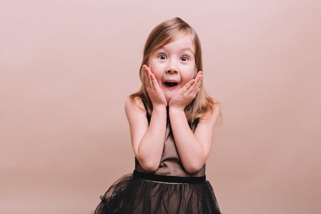 베이지 색 벽에 환상적인 놀란 감정과 함께 포즈를 취하는 위대한 사랑스러운 어린 소녀의 초상화. 열린 마우스로 포즈를 취하는 어린 소녀는 그녀의 얼굴, 진정으로 감정, 텍스트 장소에 손을 보유하고 있습니다.