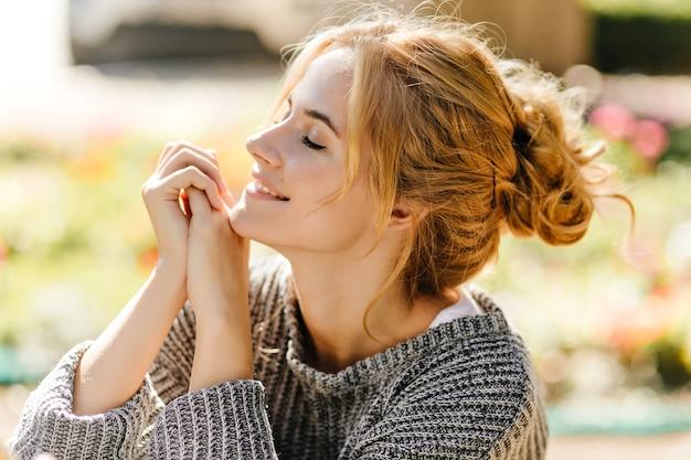 緑の家に座ってポーズをとって緑の目の赤毛の女性の肖像画