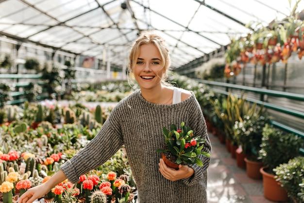植物を保持している緑色の目の若い女性の肖像画。灰色のセーターを着た女性が温室の中を歩きます。
