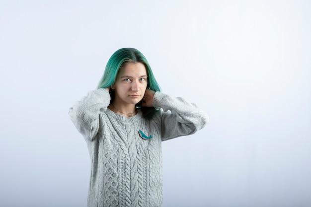 白でポーズをとる緑髪の少女の肖像画。