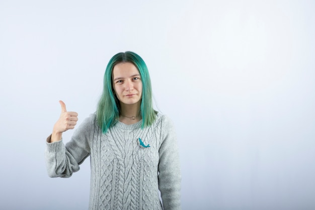 카메라에 포즈와 엄지 손가락을 포기 녹색 머리 여자의 초상화.